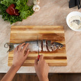 Girl cut slice of  fish to cook dinner Stock Photography