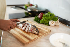 Girl cut slice of  fish Stock Photos