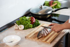 Girl cut slice of  fish to cook tasty dish Stock Photo