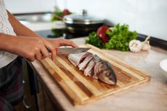 Girl cut slice of  fish Royalty Free Stock Photography