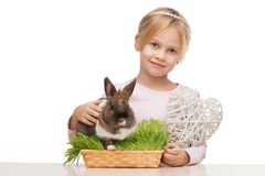 Girl with cute bunny in grass and white heart Royalty Free Stock Photos