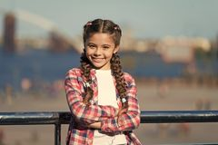 Girl cute kid with braids relaxing urban background defocused. Organize activities for teenagers. Vacation and leisure. What do on holidays. Sunny day walk royalty free stock photo