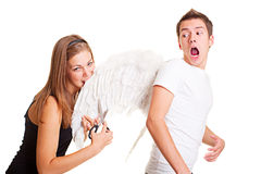 Girl cuting wings of her boyfriend. Bad girl cuting and biting wings of her boyfriend Royalty Free Stock Photos