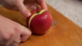 Girl cuts apple into small pieces stock video footage