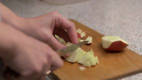 Girl cuts apple into small pieces stock video