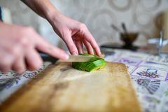 Girl cuts avocado on the board. Girl cuts green ripe avocado with knife. Fruit is cut on wooden cutting board. Side view stock images