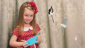 Girl cuts a blue image. Near weighs paper stock footage