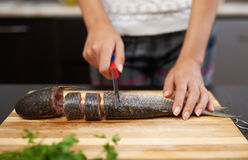 Girl cuts fish to prepare dinner Stock Photography