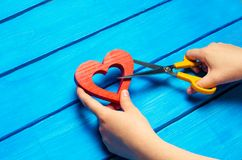 Girl cuts the heart with scissors, the concept of breaking relations, quarrels and divorce. Betrayal of the othere. blue backgroun. D stock photography