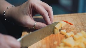 The girl cuts with a knife and boiled potatoes. Nice close-up. Slow playback. Cooking at home. Cutting board. stock footage