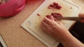 The girl cuts with a knife red fresh meat on the board and prepares cooking food. The girl cuts with a knife red fresh meat on the board and prepares cooking stock video footage