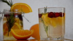 Girl cuts an orange to make detox water with orange, cranberry and rosemary, healthy drink for the diet, vitamin C