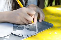 A girl cuts out a cardboard knife with stationery knife stock photography