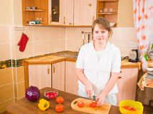 The girl cuts red tomatoes Royalty Free Stock Photos