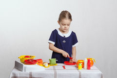 Girl cuts a toy mushroom in the kitchen Royalty Free Stock Images