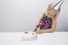 Girl cutting birthday cake at table in house Royalty Free Stock Photos