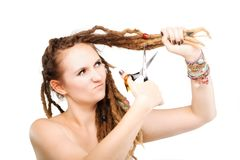 Girl cutting her dreadlocks. Portrait of a caucasian girl with scissors about to cut her dreadlocks Stock Photo