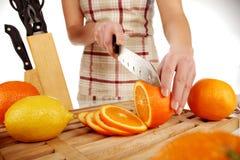 Girl cutting orange closeup Stock Photos