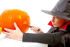 Girl is cutting pumpkin face Stock Photo