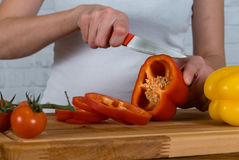 Girl cutting red paprika for salad Stock Image