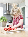 Girl cutting tomatoes Royalty Free Stock Photo