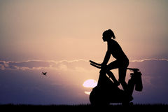 Girl with cyclette at sunset Royalty Free Stock Image
