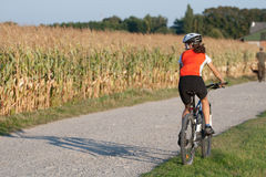 Girl cycling. On the mountain bike in the full outfit stock photography