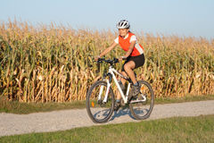 Girl cycling. On the mountain bike in the full outfit stock images