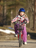 Girl cycling. Little girl is cycling in spring time Royalty Free Stock Images