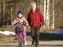 Girl cycling. Little girl is cycling and her mother is running behind Royalty Free Stock Photography