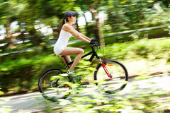 Girl cycling. In the park. She's wearing white sport clothes, cap, her bicycle is red. It's a sunny summer day. Motion blured image Royalty Free Stock Images
