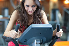 Girl  is cycling in fitness hall Royalty Free Stock Photos