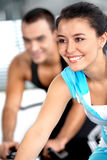 Girl cycling in a gym Stock Images