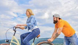 Girl cycling while man support her. Feel impulse to start moving. Woman rides bicycle sky background. Push and promoting. Girl cycling while men support her royalty free stock photo