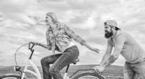 Girl cycling while man support her. Support helps believe in yourself. Feel impulse to start moving. Woman rides bicycle. Girl cycling while men support her stock photos