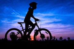 Girl cycling at mountain twilight time Stock Photos