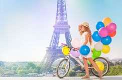 Girl cycling through Paris with balloons bouquet Royalty Free Stock Photo