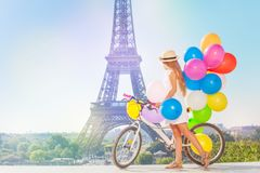 Girl cycling through Paris with colorful balloons Stock Photography