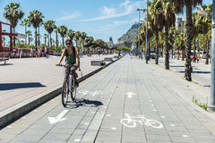 Girl cycling on the promenade in Barcelona Stock Photo