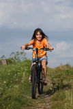 Girl cycling  in rural scenery Stock Images