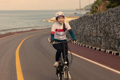 The girl cycling uphill on the  road. Royalty Free Stock Photos