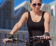 Girl cycling in urban environments Stock Photos