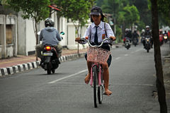 Girl cycling in Yogyakarta Stock Photo