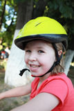 Girl cyclist in a bicycle helmet on the park, cute simle Royalty Free Stock Images
