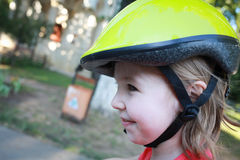 Girl cyclist in a bicycle helmet on the park Royalty Free Stock Image
