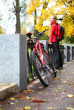 Girl cyclist with bike and backpack on bridge in autumn park Stock Photo