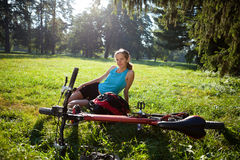 Girl cyclist with bike relaxation in spring park Stock Photos
