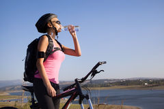 Girl cyclist drinking water. Cyclist girl drinks water from a bottle at the lake Stock Image