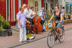 Girl cyclist and street musicians  in Amsterdam Royalty Free Stock Photography