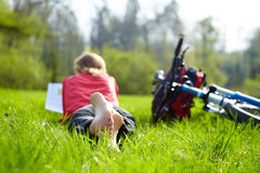 Girl cyclist on a halt reads on green grass outdoors in spring park Stock Photography